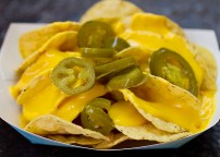 Nachos - traditional corn Tostito chips drizzled with nacho cheese sauce and topped with optional jalapeno peppers.